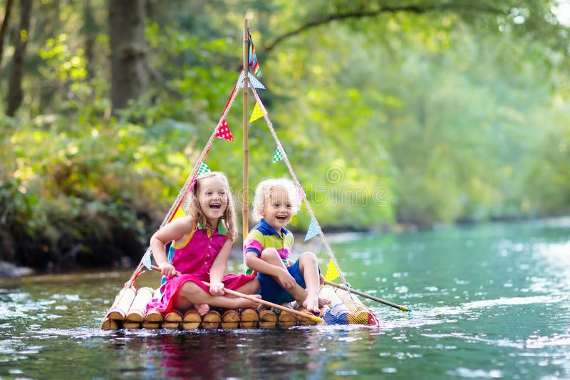 Kids on wooden raft royalty free stock photos