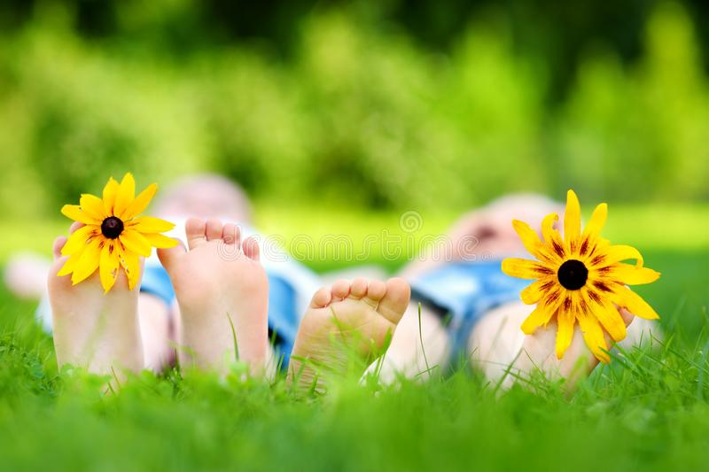 Two childrens feet on grass outdoors royalty free stock photography
