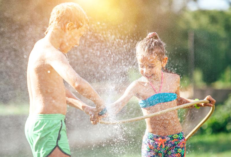 Two childs playing in garden, pours each other from the hose, makes a rain. Happy childhood concept image royalty free stock image