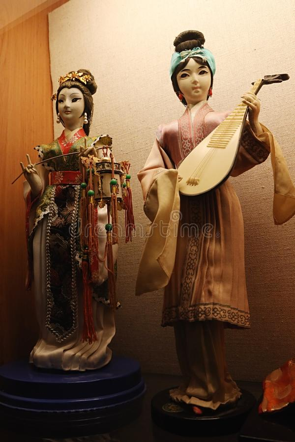 Two chinese decorative figures of women, female musician holding Pipa and second one, possibly dancer or actor, holding decorative royalty free stock photography