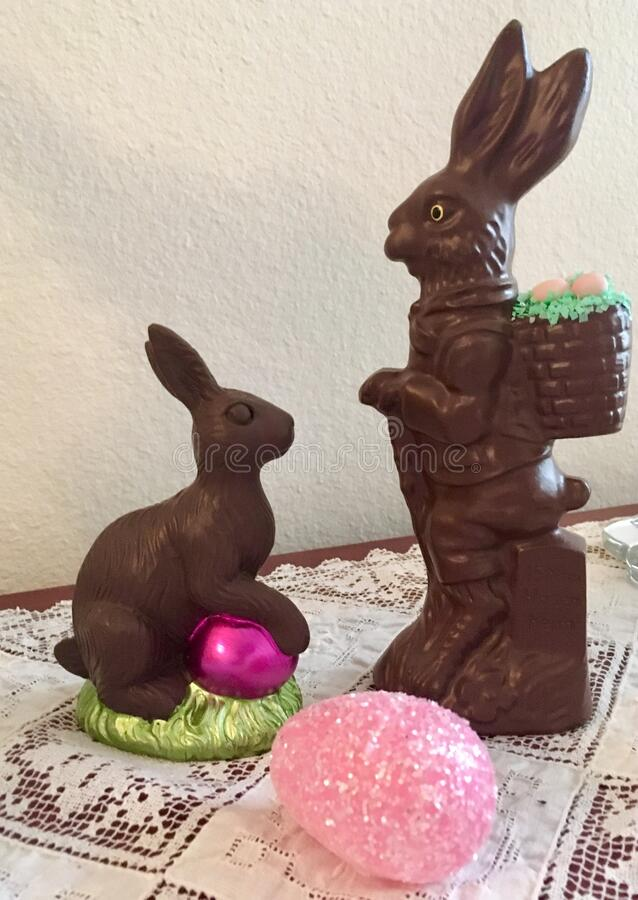 Two Chocolate Bunnies. With a pink Easter egg add fun to the holiday decor stock image