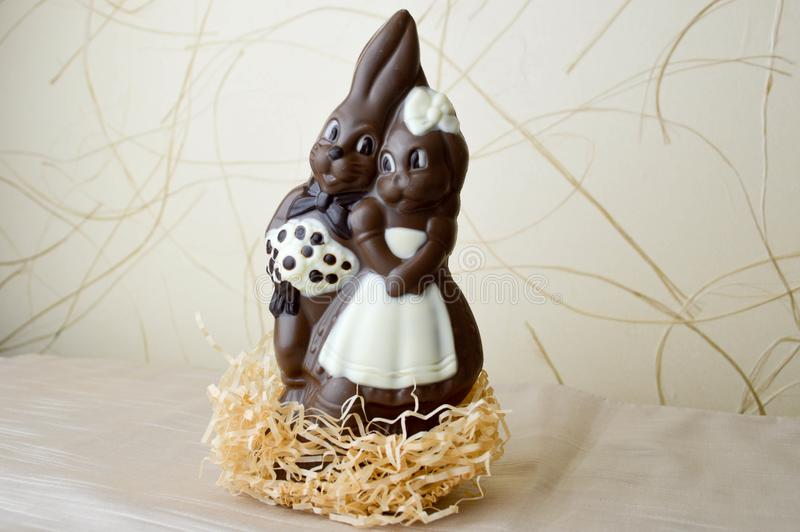 Two chocolate rabbits. Two tasty, embracing, chocolate hares, a loving couple stock photography