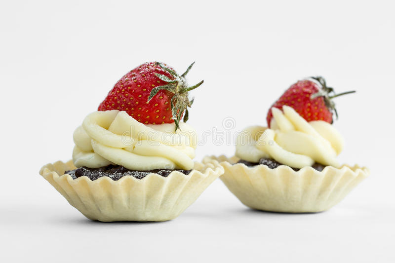Two chocolate tartlet topped with strowberry on white background. royalty free stock image