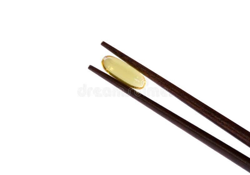 Download Two Chopsticks Holding  Omega-3 Vitamin Stock Photo - Image: 9897742