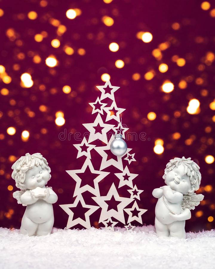 Two Christmas baby angels statuettes on snow with Christmas tree stock photo