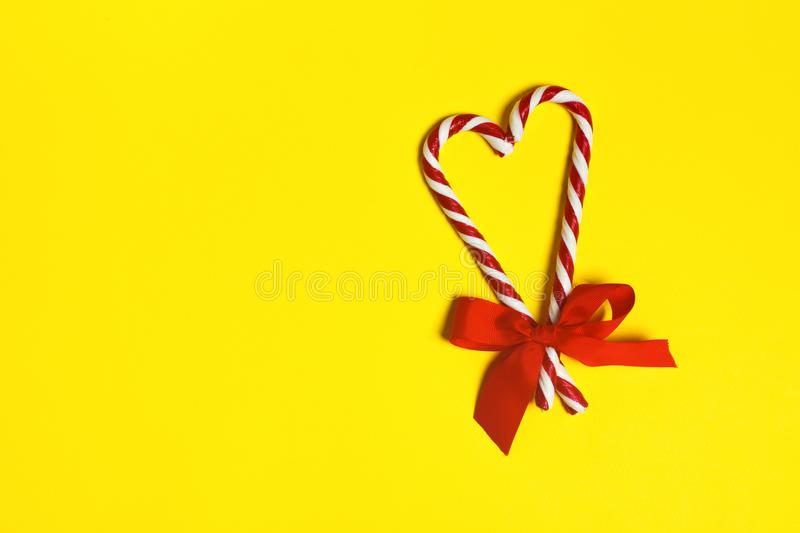 Two Christmas candy canes overlapping to form a heart and a red bow on a yellow background. copy space royalty free stock photography