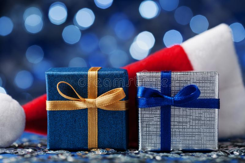 Two christmas gift box or present and santa hat against blue bokeh background. Magic holiday greeting card. royalty free stock photo