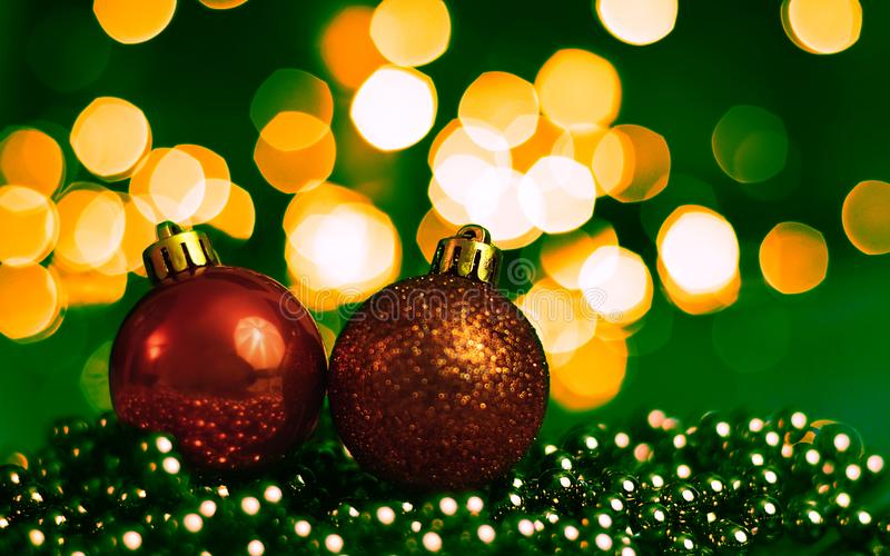 Two Christmas ornaments lying on balls of a Christmas chain on a blurred background with lights royalty free stock photography
