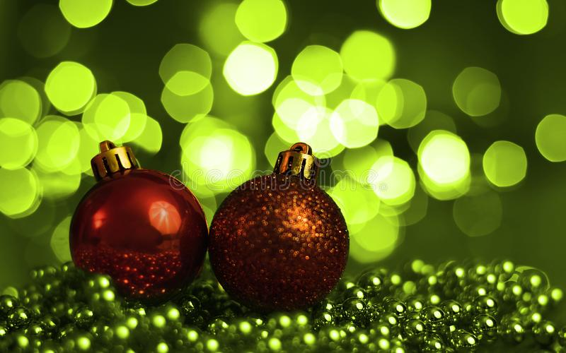 Two Christmas ornaments lying on balls of a Christmas chain on a blurred background with lights royalty free stock photo