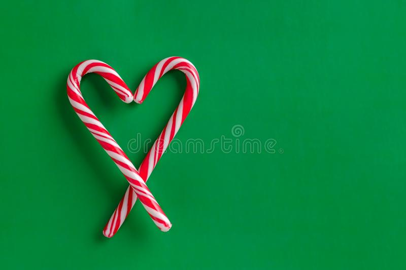 Two christmas red and white candy canes in the shape of heart on a green paper background royalty free stock images
