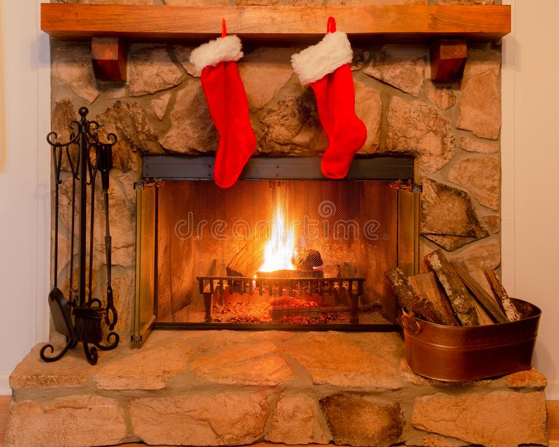 Two Christmas stockings on the mantle of a stone fireplace with a warm fire. stock photo