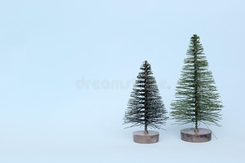 Two Christmas trees on blue background in minimal style. Christmas ornaments, new year and winter concept royalty free stock image