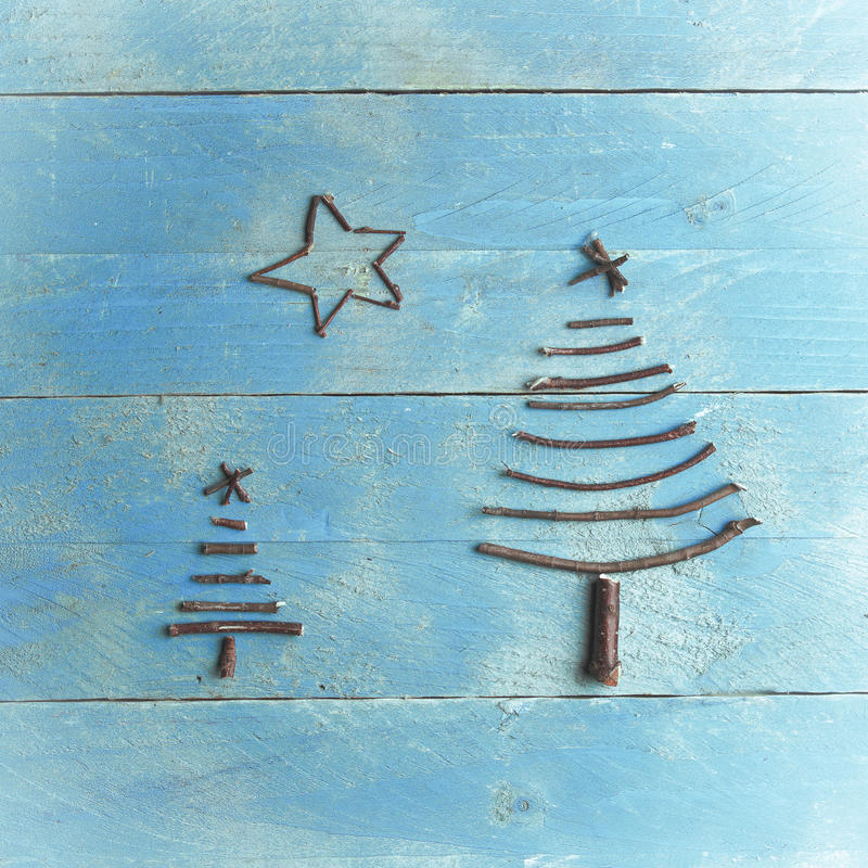 Two Christmas trees and star made from dry sticks on wooden, blue background. Christmas tree ornament, craft.  stock photography
