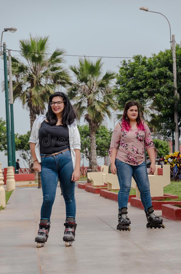Two chubby girls with inline skates in the park. Happy stock photo