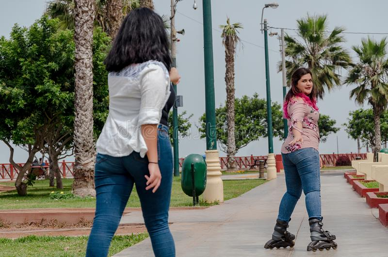 Two chubby girls with inline skates in the park. Happy stock image