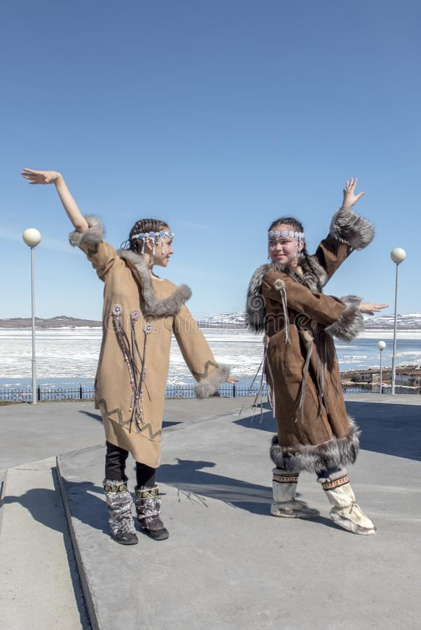 Two chukchi girls dance against Arctic landscape. Two chukchi girls in folk dress show figure of traditional dance against the Arctic landscape stock image
