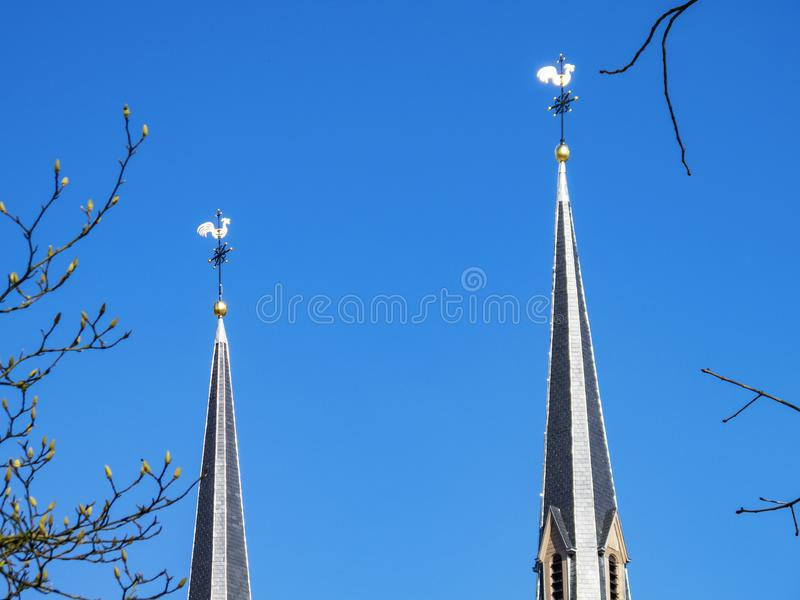 Two church spires topped by weathercocks against a clear blue sky and March budding tree branches royalty free stock image