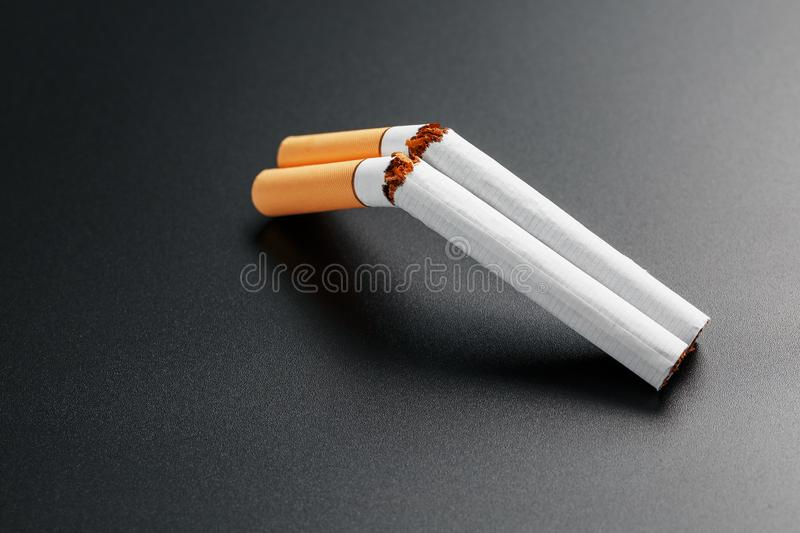 Two cigarettes in the form of a double-barreled shotgun on a black background with copy space. Stop smoking. The concept of. Smoking kills. Smoking as a deadly stock photography