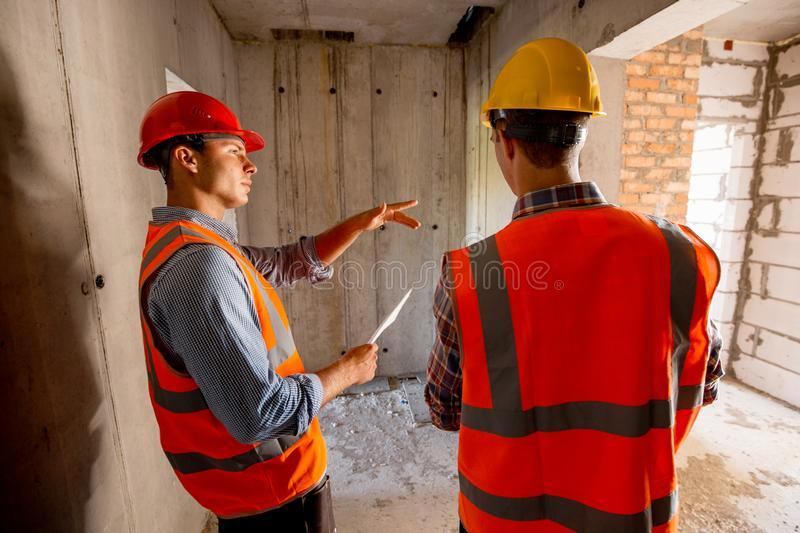 Two civil engineers dressed in orange work vests and helmets walk inside the building under construction royalty free stock photo