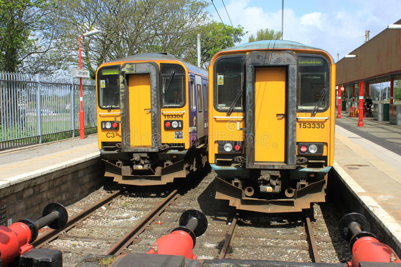 Two Class 153 diesel trains at Lancaster station. Class 153 diesel single car units in platforms 1 and 2 at the buffers at Lancaster station in Northern livery royalty free stock photography