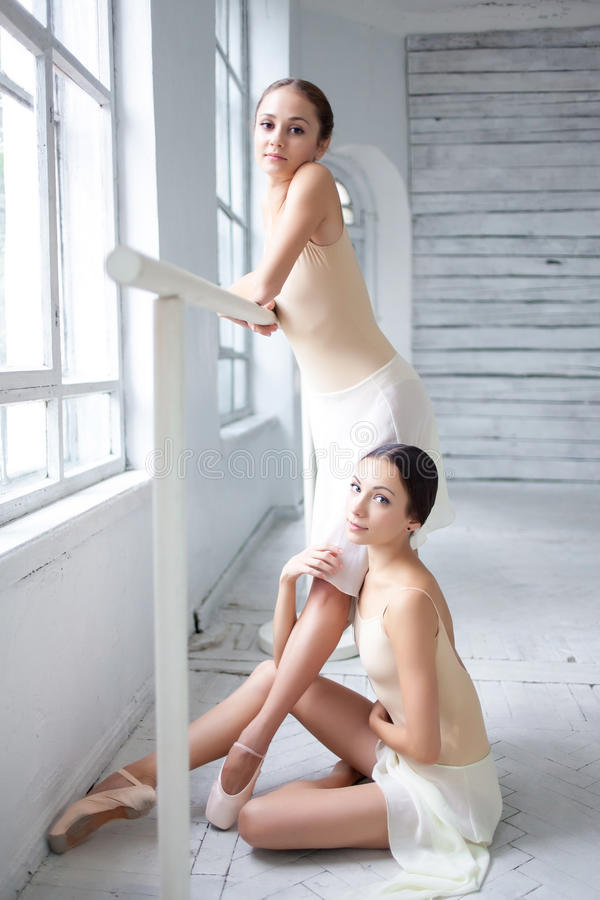 The two classic ballet dancers posing at barre royalty free stock images