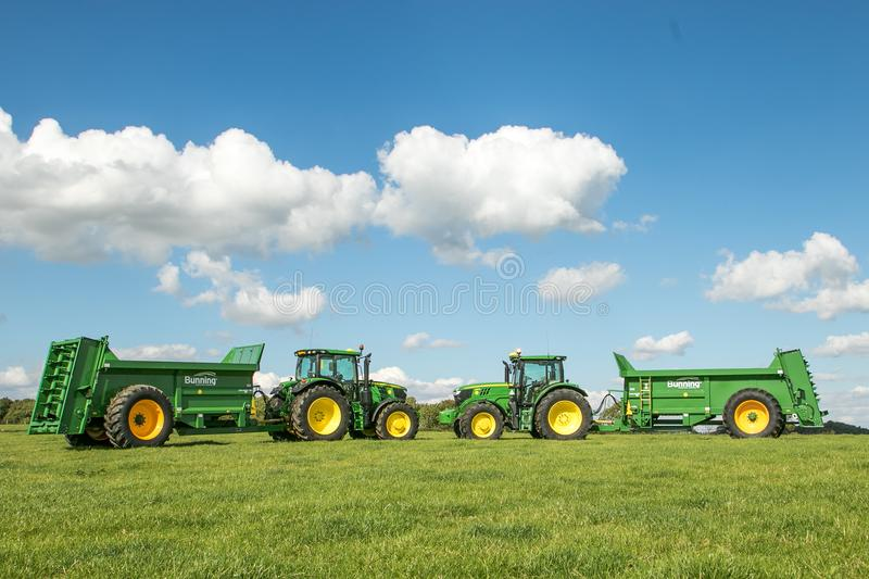 Two green John Deere tractors pulling bunning muck spreaders. Two clean green John Deere 6155r tractors pulling bunning manure spreaders parked on field with big royalty free stock photos