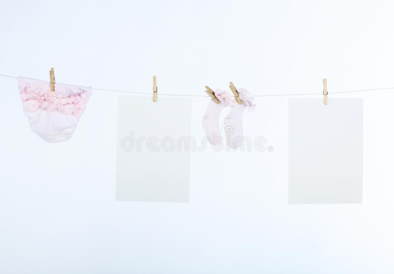 Two clean sheet of paper and babyÂ's clothes royalty free stock image