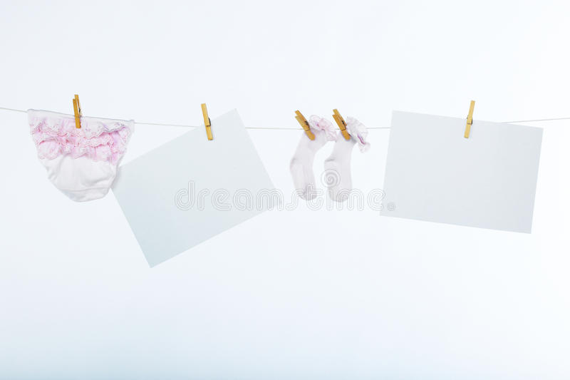 Two clean sheet of paper and babyÂ's clothes stock images
