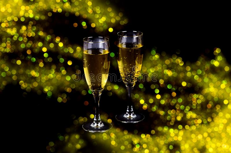 Two clear glasses of champagne filled with sparkling drink on shiny beautiful fesitive sparkling lights bokeh background. Isolated on black stock photos
