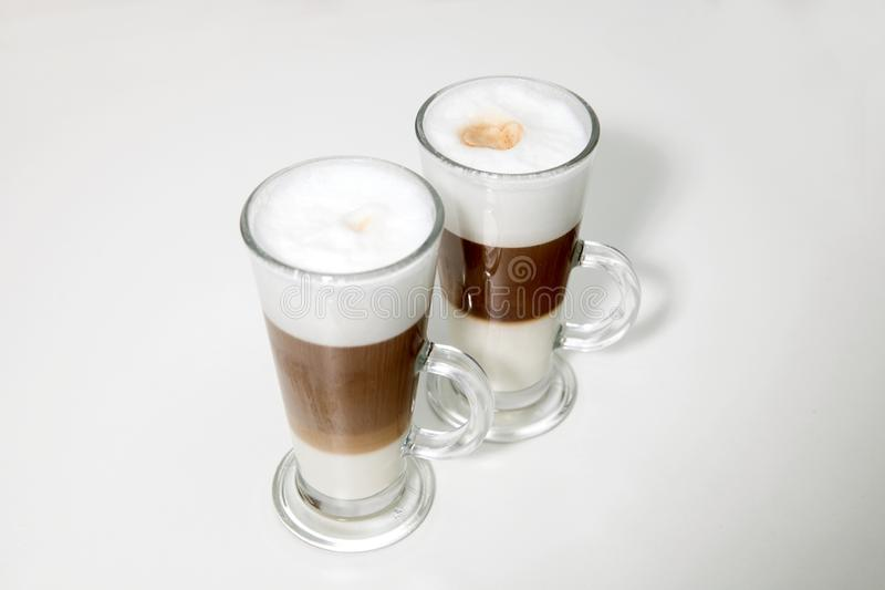 Two clear glasses of latte macchiato coffee stock images