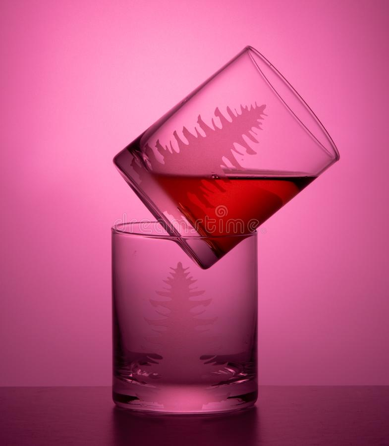 Two clear glasses pink background stock photography