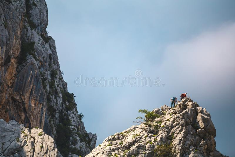 Two climbers climb to the top of the mountain stock images