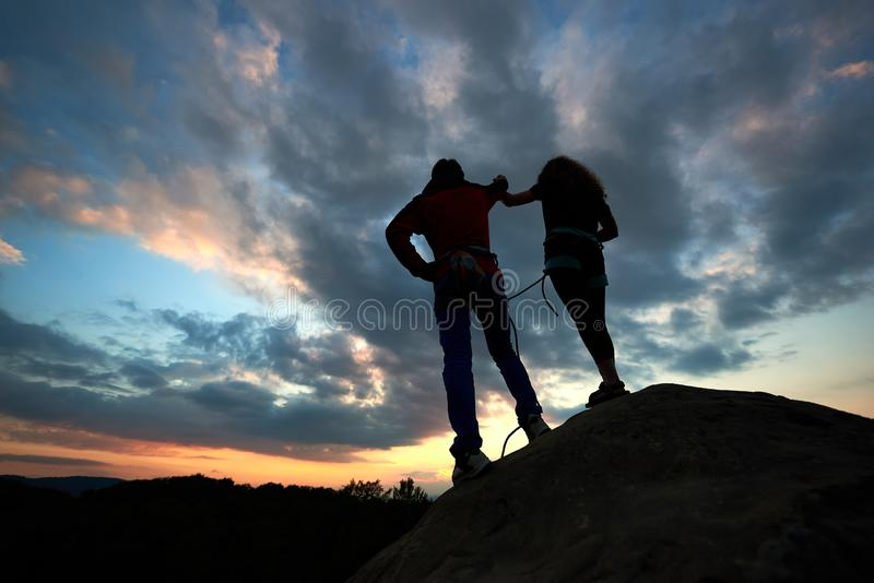 Silhouettes of man and woman look at sunset on the top of rock. Hikers couple on dramatic sky at sunset. Back view. stock photo