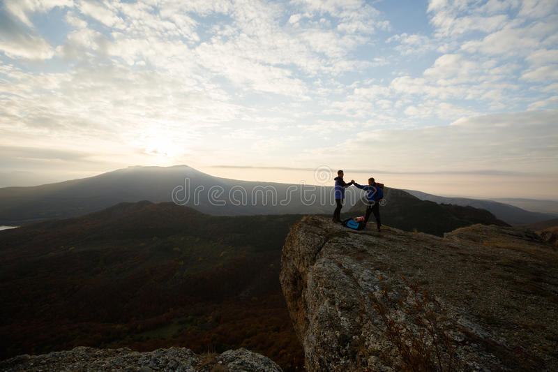 Two climbers standing on summit above clouds in the mountains holding hands. Silhouettes of hikers celebrating ascent on royalty free stock photography