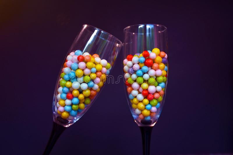 Two clinking Champagne glasses filled with small colorfull foam balls on dark black background stock photos
