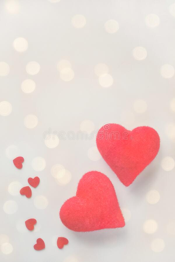 Two closeup love hearts on blurry defocused light bokeh background. Valentine`s day greeting card. Love and dating, romance concept.Copy space for text royalty free stock photography