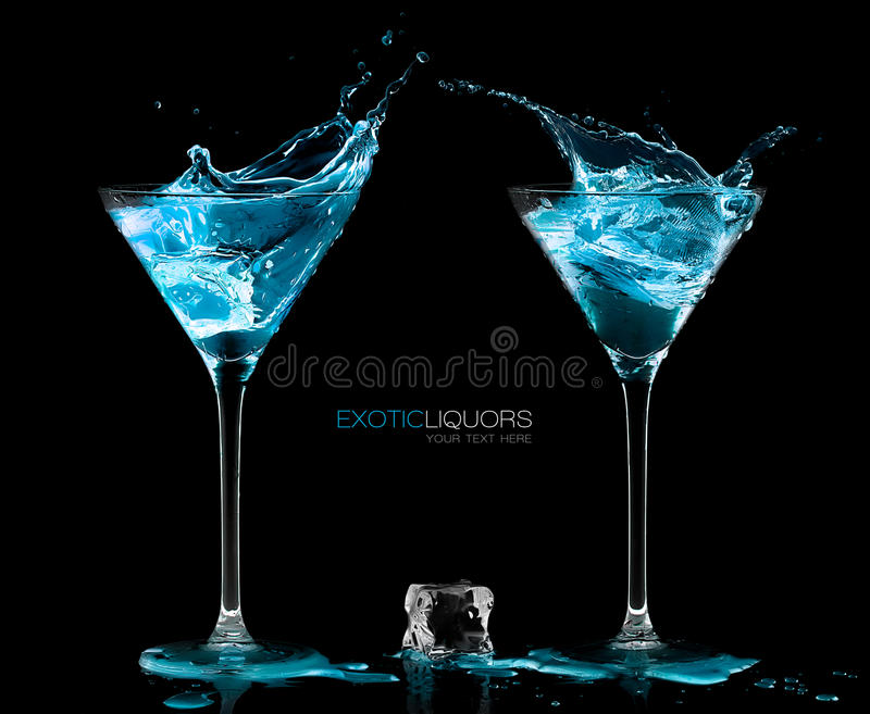 Two Cocktail Glasses with Blue Vodka. Style and Celebration Concept. Ice cube between two cocktail glasses filled with blue alcoholic exotic liqueur splashing royalty free stock photo
