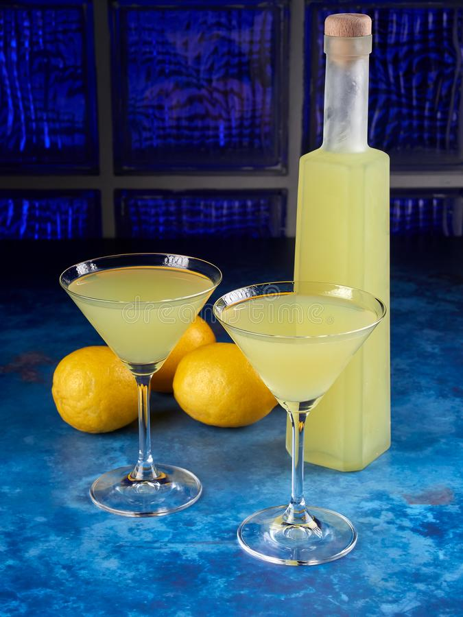 Two cocktail glasses and a bottle of traditional Italian liqueur limoncello or limoncino royalty free stock photography