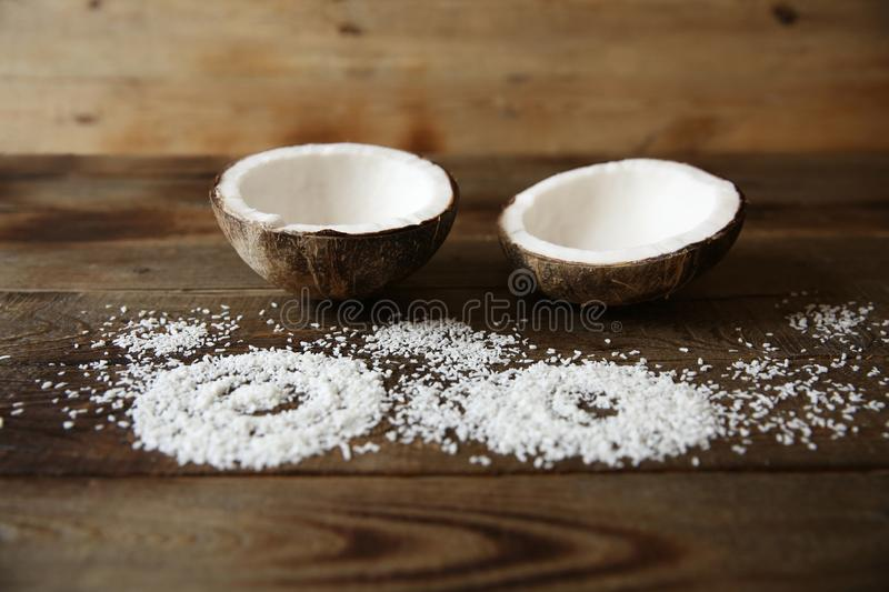 coconut halves with coconut flakes on a wooden background for beauty and spa with copy space for text royalty free stock photography