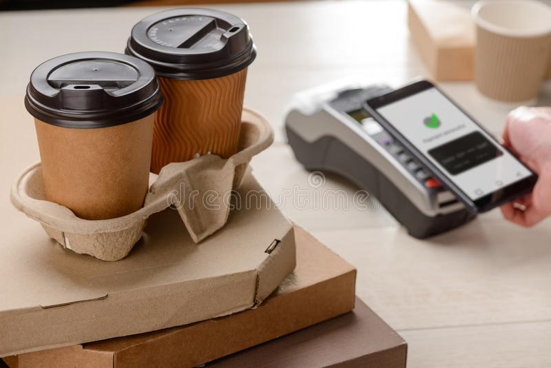 Two coffee cups. And boxes of pizza. Customer paying for purchases by a phone. Fast food and cashless payment stock photos