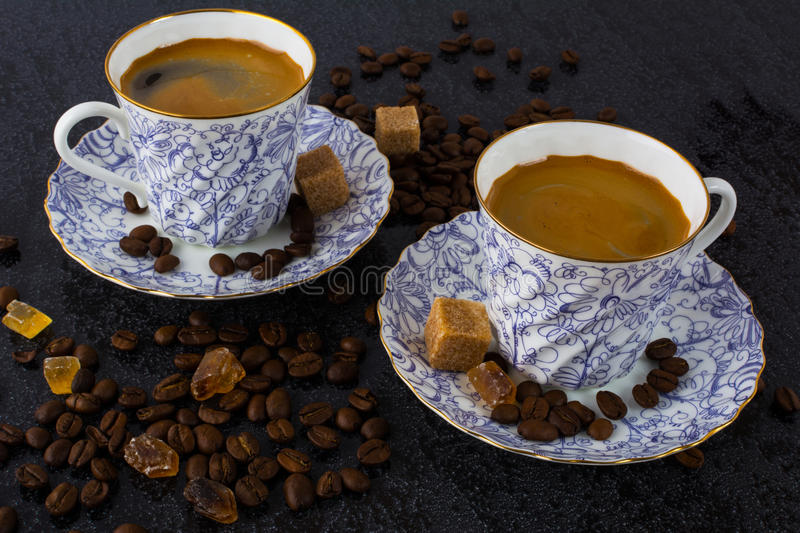 Two coffee cups on the coffee beans background stock photo