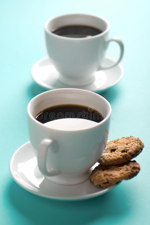 Two coffee cups with cookies. On blue background royalty free stock images