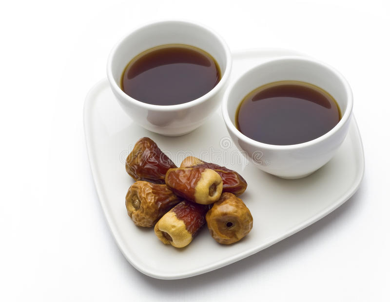 Two coffee cups and dates. Wo white cups with black coffee with dates at foreground stock photography