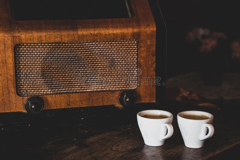 Two coffee cups with espresso and retro radio on dark wooden background. Vintage color tone stock photo
