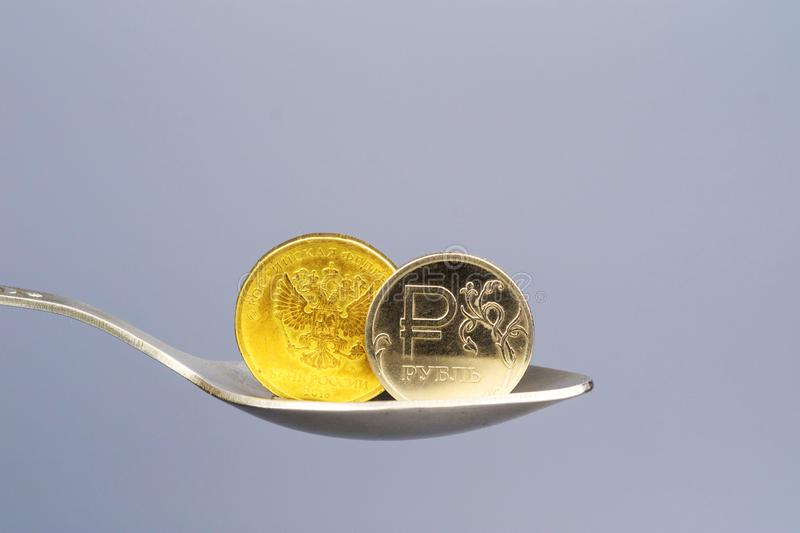 Two coins in a teaspoon, gold and silver coins Russian rubles stock photo