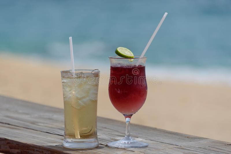 Two cold alcoholic beverages at the beach!. Two alcoholic beverages in icy glasses, on wooden deck with beach sand and surf in the background stock images