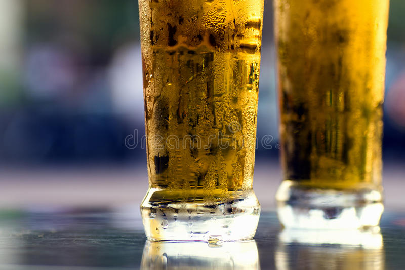 Two cold beers. Two cold lager light beers on table on blue background stock image