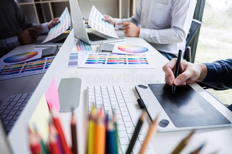 Two colleague creative graphic designer working on color selection and color swatches, drawing on graphics tablet at workplace wi. Th work tools and accessories stock photo