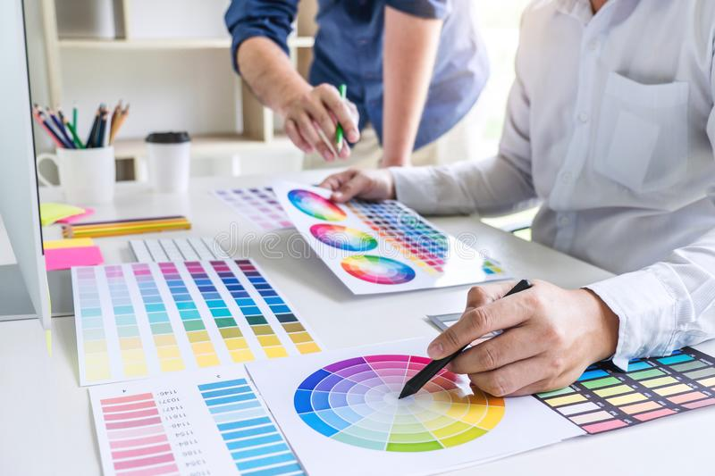 Two colleague creative graphic designer working on color selection and color swatches, drawing on graphics tablet at workplace wi royalty free stock images