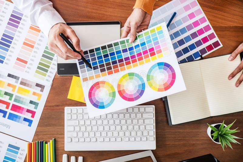 Two colleague creative graphic designer working on color selection and color swatches, drawing on graphics tablet at workplace wi stock photography